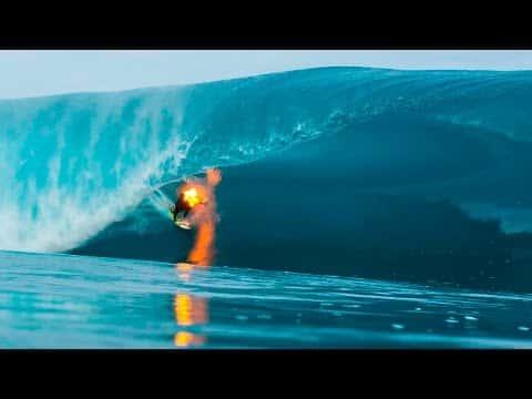 Er zündet sich den Rücken an. Dann stellt er sich auf sein Surfbrett und reitet die Wellen.