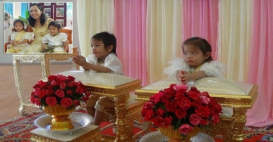 This is the bizarre moment a pair of three-year-old twins who were ''soulmates in a past life'' get married - to ward off bad luck.  Brother and sister Teekatat and Tawisa Hiranmekawanit (corr) tied the knot in a traditional ceremony in Ang Thong province, centralThailand.  Parents believe the smiling toddlers were lovers in a previous life but were separated by a terrible tragedy.   They were reincarnated together as twins and have to get married to show ''angels'' that they are in love and be together forever, according to mother-of-the bride AND groom Sasi Hiranmekawanit.  ''They must get married otherwise one of them will die,'' she said.  ''We provided the wedding ceremony according to our belief that in the olden days the boy and girl twins were soulmates but couldn't stay together.  ''They were reborn again in this life, they were reborn as boy and girl twins.''  Teekatat  and Tawisa are both three years and four months old.   The bride wore a traditional Thai wedding dress with a gold sarong a gold sash. While the groom was dressed in a white shirt, gold pants and a green sash.  They boy even handed a sinsod - payments made by men to the families of the bride - of 22,000 THB (£450) and 30.5g of 23 karat gold.  Villagers and relatives joined the twins and the parents for the ceremony in the Wiset Chai Charn district of Ang Thong.  Beamig mother Sasi added: ''There was a very relaxed and nice atmosphere. The local community helped us.  ''As parents we must provide the wedding to let the angels know that the twins are happily in love and will be together forever.  ''It is an ancient belief to show the angels they are in love and will never stay apart.''  Despite the formal ceremony, the children won't be married in law. They are also likely to find and marry their own partners when they get older.